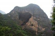 Mohutná jeskyně otevřená ve stěně vápencové hory.